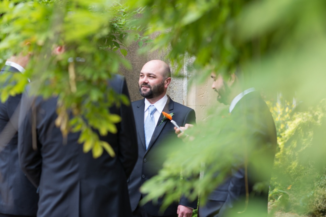 framed by leaves, groom, nervous, ceremony, pre-wedding